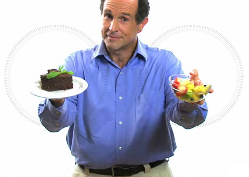 A middle aged man offering a piece of cake and a bowl of fruit.