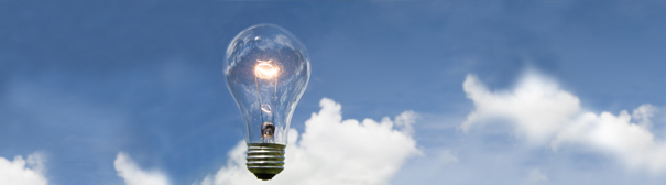 A lit lightbulb floating in front of a blue sky with a large puffy white cloud.