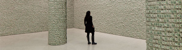 A woman looking at a Guggenheim art exibit where an entire room is wallpapered with 100,000 $1 bills.