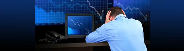 A man, head in hands, sitting in front of a monitor depicting a stock crash.