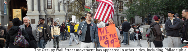 "Occupy Wall Street protesters holding an American flag and a sign reading ""We are the 99%"""