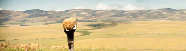 Photo: Person carrying hay sack on top of head