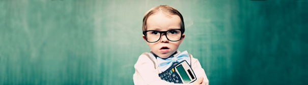 Young child wearing large glasses and holding a calculator.