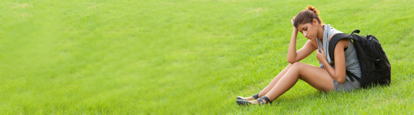 A woman wearing a backpack sitting on a grassy hill.