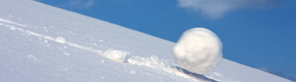 A giant snowball rolling down a snow covered hill.