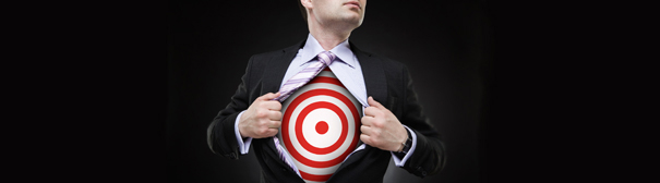 A man pulling open his dress shirt (Superman-Style) revealing a bullseye on his chest.