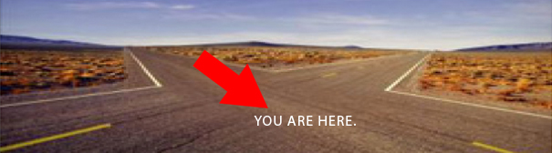 "A four way intersection in the desert with a red arrow labeled ""You are here."""